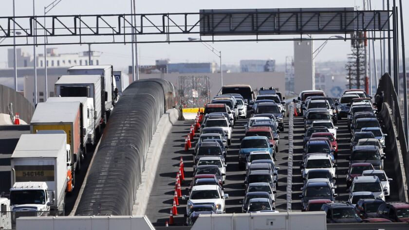 FILE - In this March 29, 2019, file photo, vehicles line up to enter the U.S. from Mexico at a borde