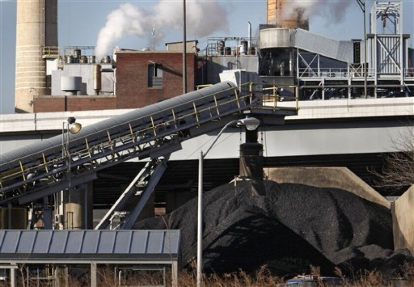 """Coal is piled beside the Capitol Power Plant, a coal-burning electrical plant, in Washington, on Wednesday, Feb. 25, 2009. The plant cannot be retrofitted to meet new """"global warming"""" environmental standards. (AP Photo/Jacquelyn Martin)"""