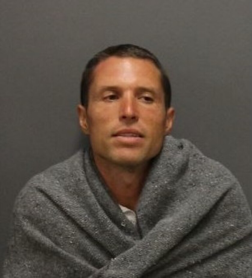 Booking photo of a white man with brown hair wrapped in a grey blanket, looking away from the camera.