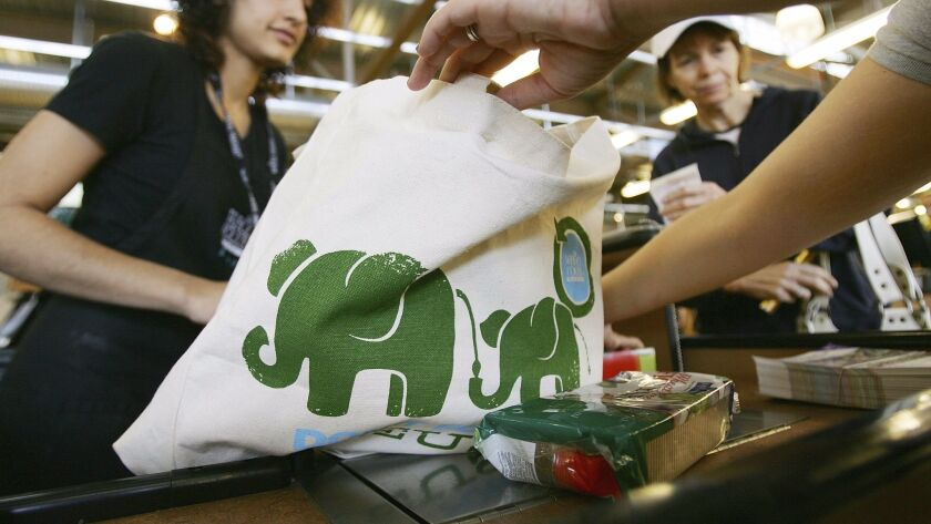 A cashier hands out free reusable grocery bags at a Whole Foods Market in Pasadena, Calif. on April 22, 2008.