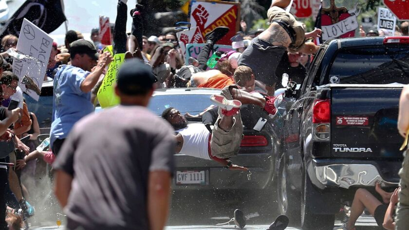 FILE - In this Aug. 12, 2017 file photo, people fly into the air as a vehicle is driven into a group
