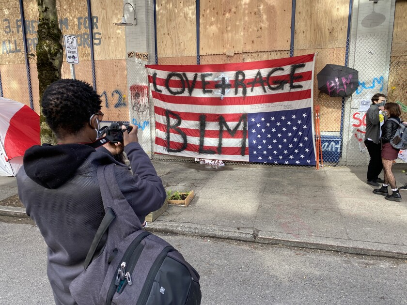 A man photographs an upside-down flag June 13 on a wall of the precinct that police deserted in Seattle's protest zone.