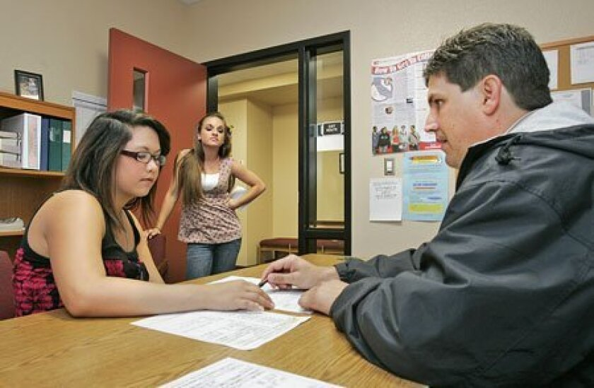 At El Camino High School in Oceanside, counselor Randy Thomas met with 11th-grader Alex Navalta (left) to go over her class schedule for next year. Next in line was 11th-grader Stacey Brizeno. (Charlie Neuman / Union-Tribune)