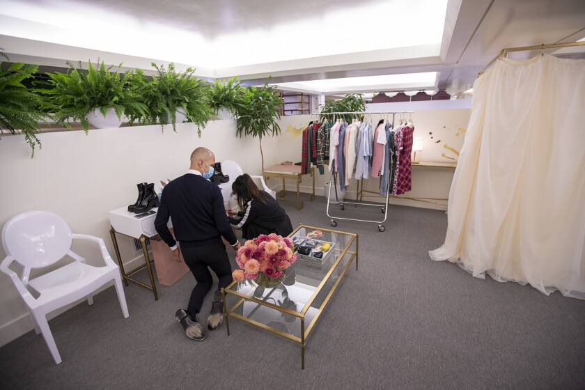 Rob Alvarez, left, and Katrina He, working for Miu Miu, prepare for a client at South Coast Plaza's the Pavilion on Friday.