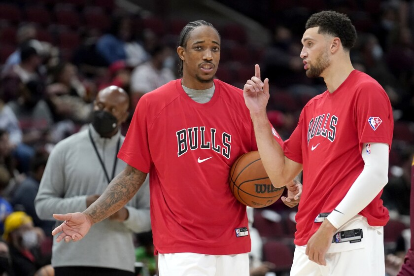 during the Chicago Bulls' DeMar DeRozan, left, and Zach LaVine talk during warm ups before the start of the second half of an NBA preseason basketball game against the Cleveland Cavaliers Tuesday, Oct. 5, 2021, in Chicago. (AP Photo/Charles Rex Arbogast)