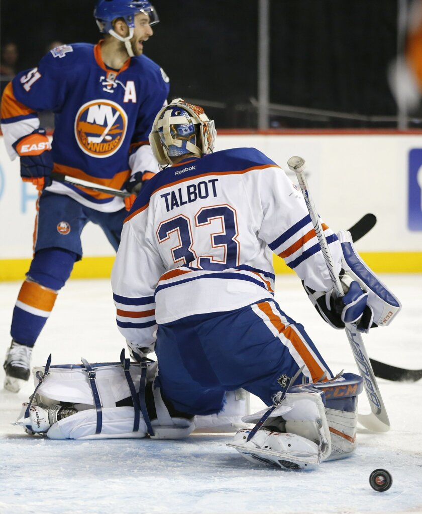 New York Islanders center Frans Nielsen (51), of Denmark, looks back as the puck rolls out of the crease behind Edmonton Oilers goalie Cam Talbot (33) after Islanders' Kyle Okposo (not shown) scored in the second period of an NHL hockey game in New York, Sunday, Feb. 7, 2016. (AP Photo/Kathy Willen