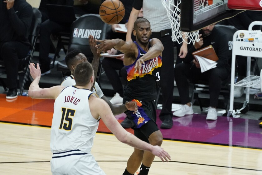 Phoenix Suns guard Chris Paul (3) passes as Denver Nuggets center Nikola Jokic (15) defends during the second half of Game 1 of an NBA basketball second-round playoff series, Monday, June 7, 2021, in Phoenix. (AP Photo/Matt York)