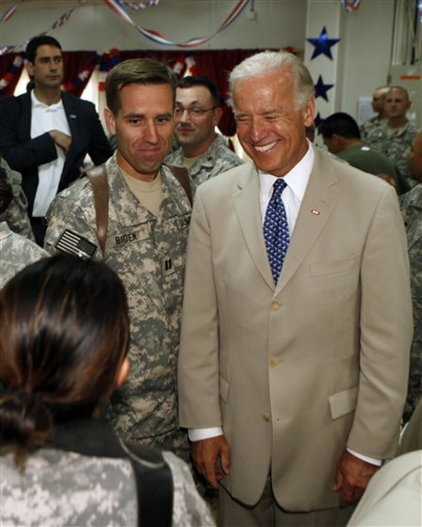 U.S. Vice President Joe Biden, right, is seen with his son, U.S. Army Capt. Beau Biden, left, at Camp Victory on the outskirts of Baghdad, Iraq, Saturday, July 4, 2009. Biden celebrated the Fourth of July with his son and other American troops in Iraq on Saturday, a day after warning Iraqi leaders that U.S. assistance will be jeopardized if the country reverts to ethnic and sectarian violence. Biden began Independence Day by greeting more than 200 U.S. soldiers who were becoming American citizens at a naturalization ceremony in a marble domed hall at one of Saddam Hussein's palaces at Camp Victory, the U.S. military headquarters on the outskirts of Baghdad. (AP Photo/ Khalid Mohammed, Pool)