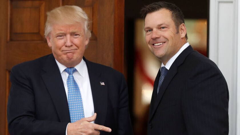 President-elect Donald Trump greets Kansas Secretary of State Kris Kobach as he arrives at the clubhouse of the Trump National Golf Club, Bedminster, in Bedminster, N.J., on Nov. 20.