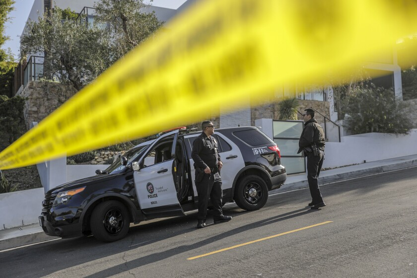 LAPD officers close a road leading to the Hollywood Hills home where rapper Pop Smoke was fatally shot Wednesday morning.