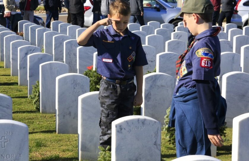 Cub Scout Trey Pavlik of Cub Scout Pack 616 in Scripps Ranch, left, along with a fellow scout, salutes after placing a holiday wreath on one of the graves at Miramar National Cemetery.