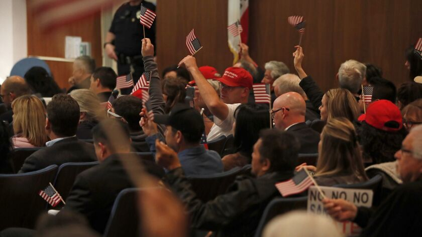Opponents of Senate Bill 54 cheer and wave American flags during a Costa Mesa City Council meeting o