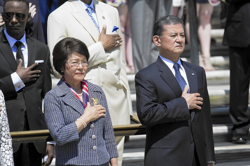 Veterans Affairs Secretary Eric K. Shinseki and his wife, Patricia, attend a Memorial Day ceremony at Arlington National Cemetery in Virginia.