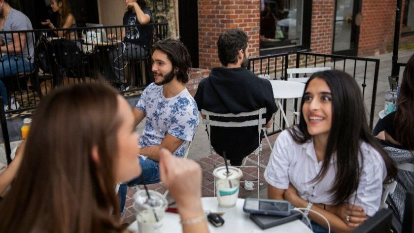 Jesse Margolis, with back to camera, sits among customers at Alfred Coffee Melrose Place in Los Angeles. Will their conversations end up on Overheard LA, the popular Instagram account he founded?
