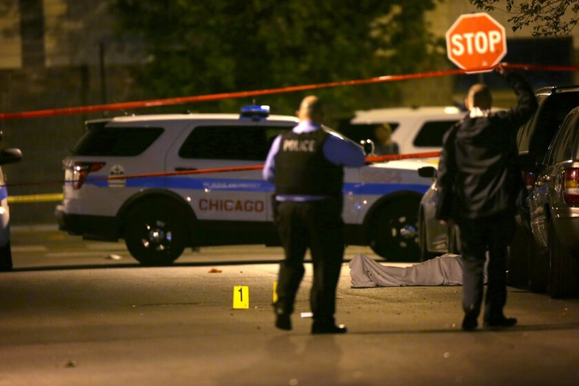 In this Monday, May 30, 2016 photo, police work the scene where a man was fatally shot in the chest in Chicago's Washington Park neighborhood.  Chicago rung in the unofficial start to summer with dozens of shootings that killed several people and wounded others over Memorial Day weekend. (E. Jason