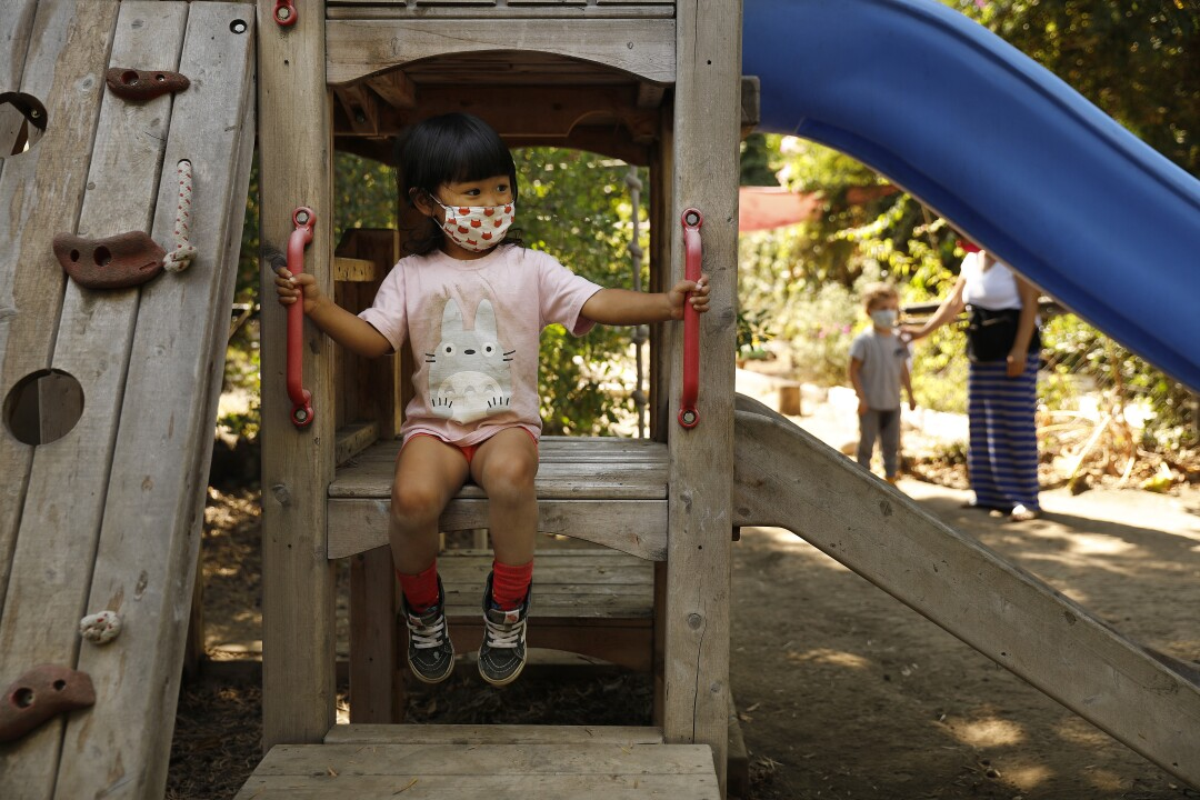 L A child wears a mask while playing at Voyages Preschool.