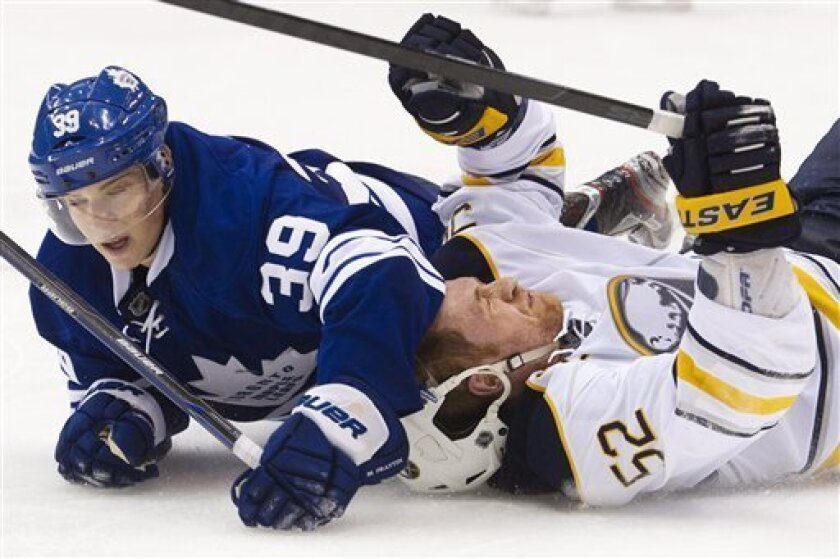 Toronto Maple Leafs forward Matt Frattin, left, takes down Buffalo Sabres defenseman Alexander Sulzer, right, during the second period of an NHL hockey game in Toronto on Saturday, March 31, 2012. (AP Photo/The Canadian Press, Nathan Denette)