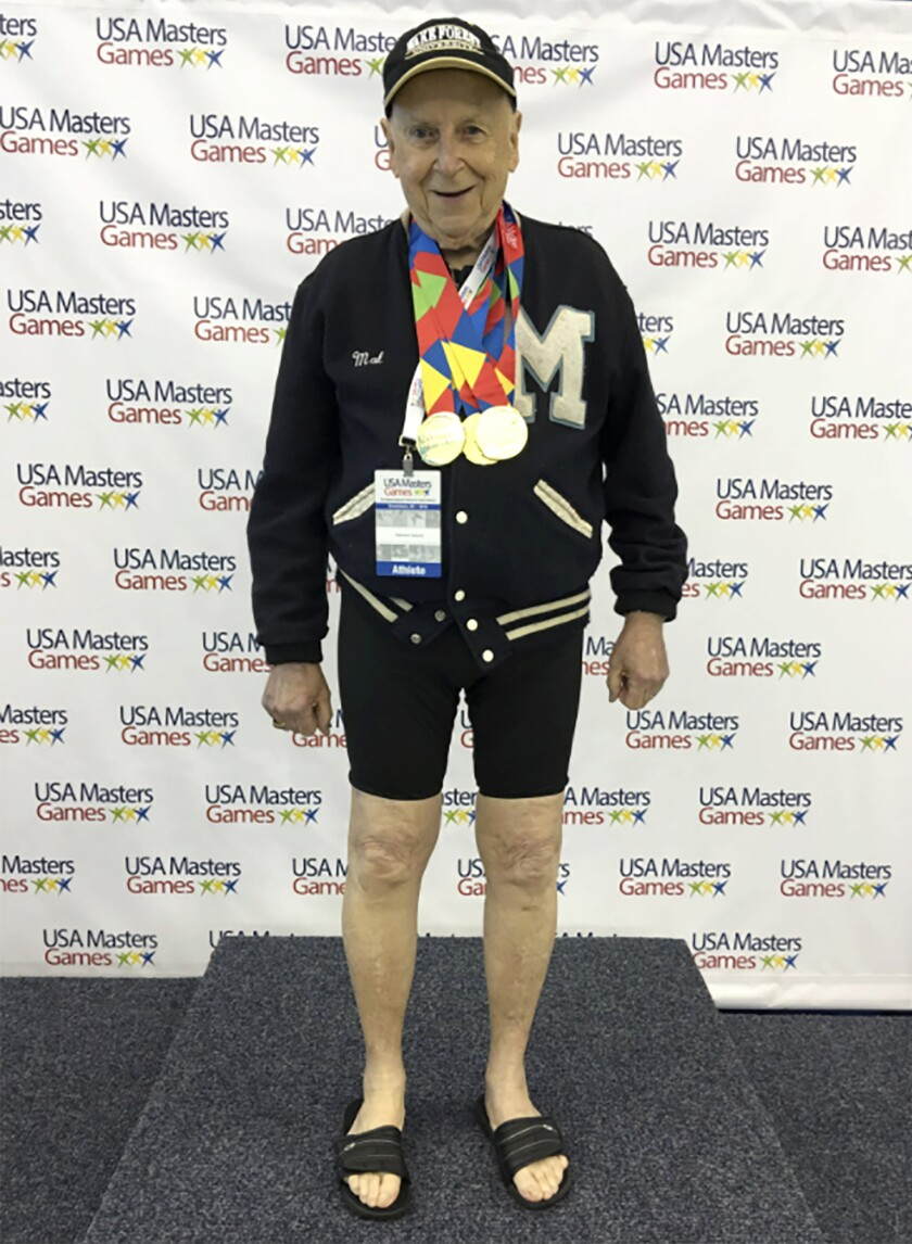 In this 2016 photo provided by Beverly Amick, her father Mal Osborn, 92, of Winston-Salem, N.C., wears a treasured 1952 letter jacket from the University of Maine, which he earned as a track athlete, while posing at a Master's swim tournament where he won multiple gold medals. He lost the jacket in October, and with the help of a post online, it was found and returned to him. (Beverly Amick via AP)