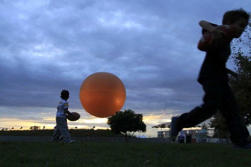 With the signature orange balloon in the background, children play as the sun sets at the Great Park in Irvine.