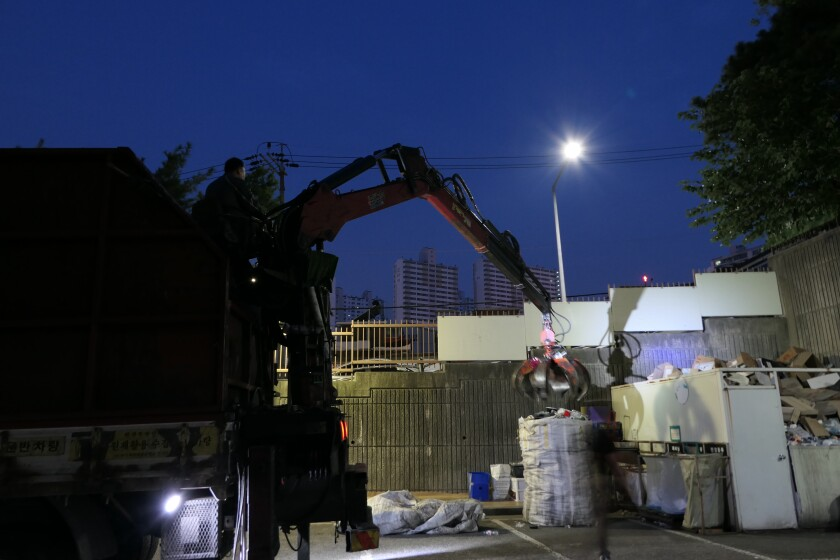 An operator uses a claw on a garbage truck to collect a bag of recyclables in Seoul.