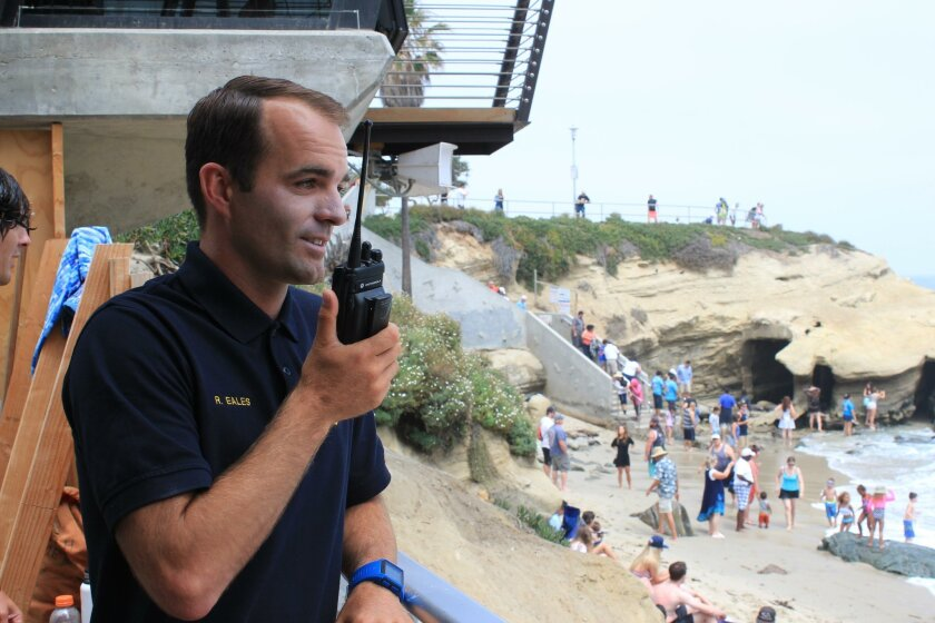 Rodger Eales communicates current beach conditions through his walkie-talkie.