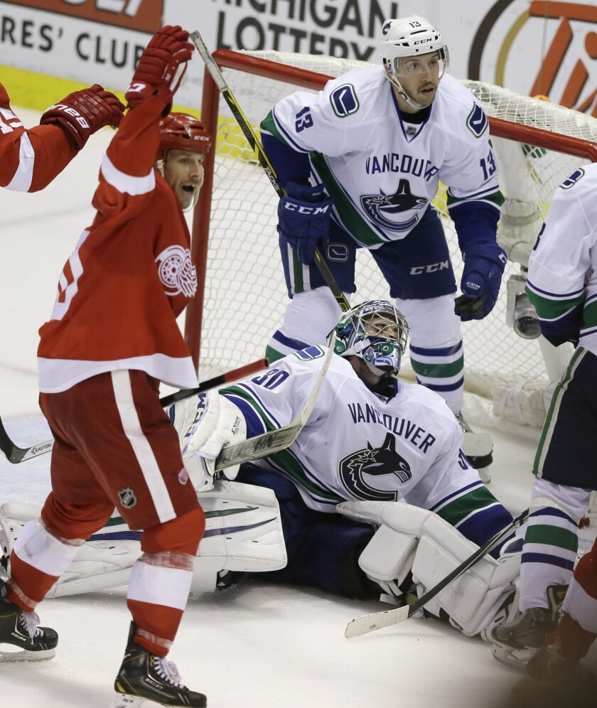 Detroit Red Wings center Stephen Weiss, left, reacts after teammate center Pavel Datsyuk scored against Vancouver Canucks goalie Ryan Miller (30) during the second period of an NHL hockey game in Detroit, Sunday, Nov. 30, 2014. (AP Photo/Carlos Osorio)