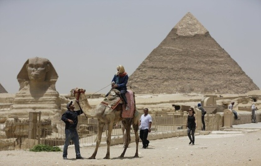 A tourist takes a camel ride at the pyramids in Giza, Egypt. The U.S. Embassy in Cairo recently warned Americans about their safety in the area.
