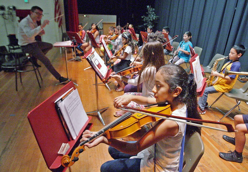In this July 2015 file photo, Alondra Cruz, 10, of Glendale, begins to play a song, following conductor Dr. Luis Zuniga's direction at the Caesura Music Camp and at Roosevelt Middle School. Caesura Youth Orchestra began in spring, and some students participated in a first summer camp that led up to a performance alongside La Sierra University music students.