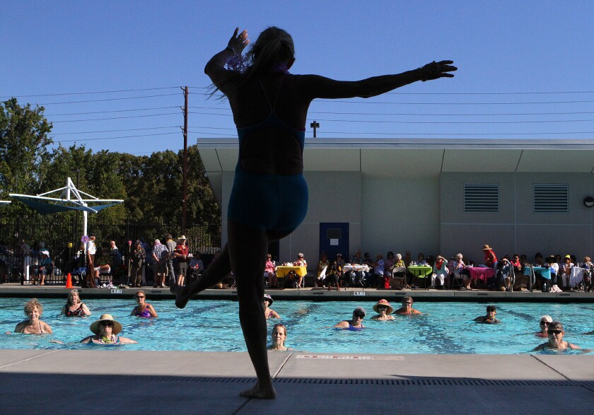 """Deni King, an adult fitness instructor, leads a water aerobics routine at Verdugo Pool for the first ever """"Rock-a-Hula"""" pool party for local seniors in Burbank on Thursday, August 21, 2014. Nearly 200 older adults came out to the event."""