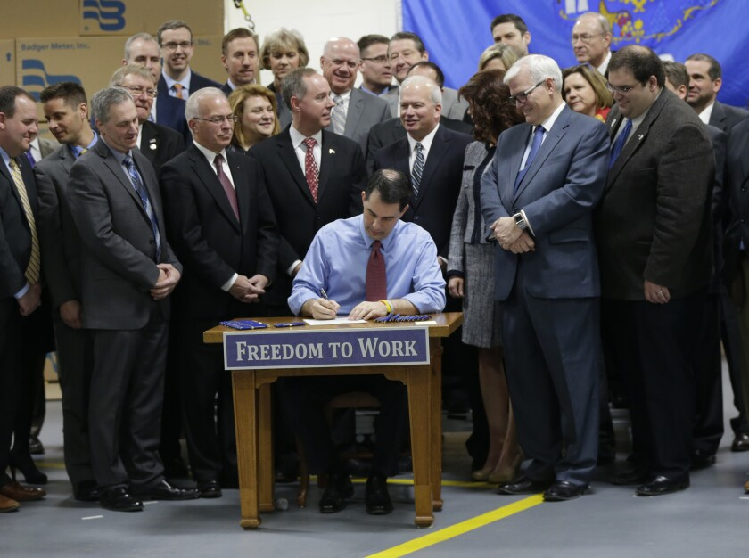 Then-Wisconsin Gov. Scott Walker signs a right-to-work bill in 2015. Democratic presidential candidates Elizabeth Warren and Bernie Sanders favor prohibiting such anti-union state laws.