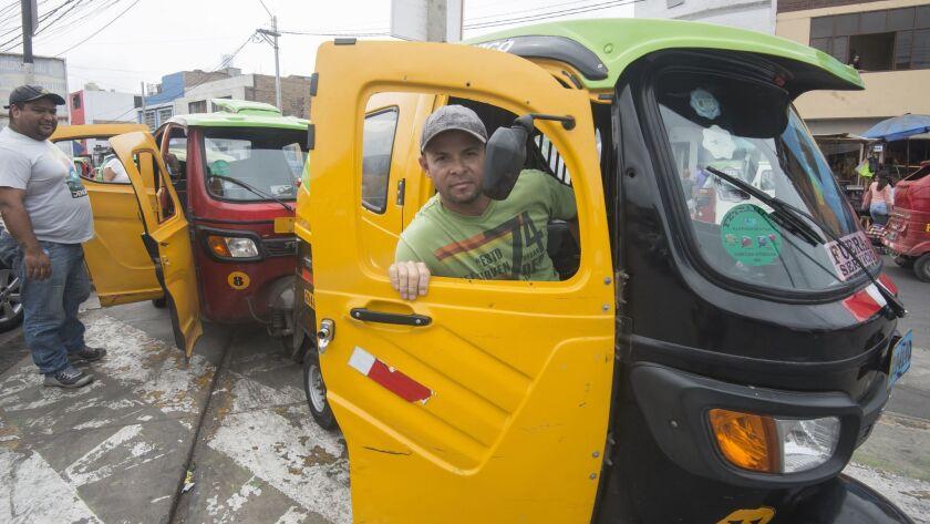 "Wilfredo Arceno, foreground, in his ""mototaxi"" in Lima, Peru."
