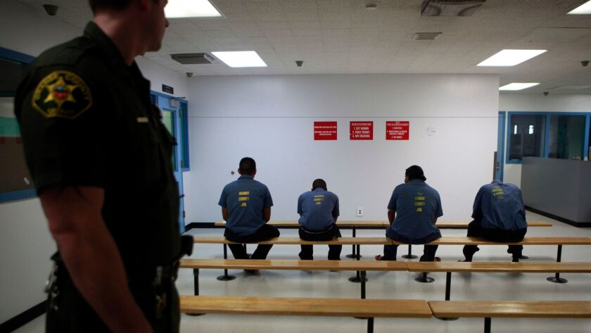 An Orange County Sheriff's deputy keeps a watch over a group of immigration detainees in the medical and dental care area at the Theo Lacy Facility in Orange.