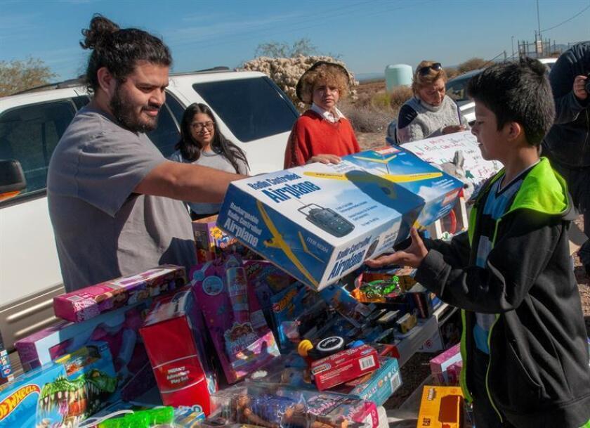 Voluntarios del Grupo Puente acuden hoy a las afueras del Centro de Detención de Eloy, en Arizona, para regalar juguetes de Navidad a los niños que acuden a visitar a sus familiares ahí recluidos. EFE