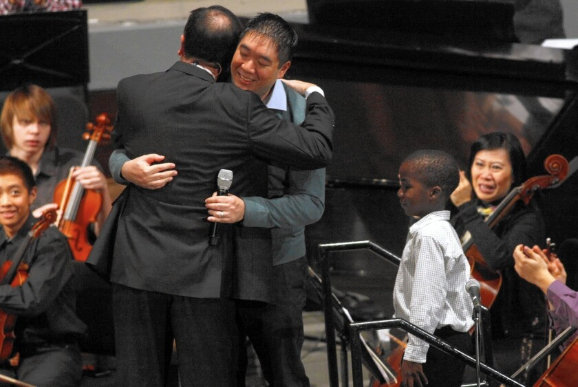 Matt Huang gets a hug from Pastor Greg Waybright on the family's return to their church, Lake Avenue Church in Pasadena.