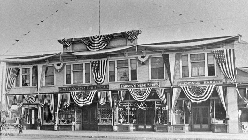 This building, festively draped with bunting and flags, stood on Broadway and housed the Shaver Groc