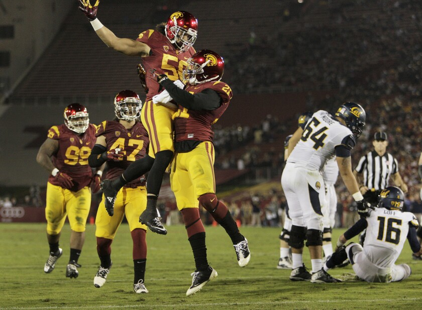 USC safety Su'a Cravens (21) celebrates with linebacker Anthony Sarao (56) after a sack against California on Nov. 13. 2014.