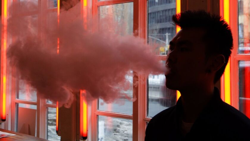 FILE - In this Feb. 20, 2014, File photo, a patron exhales vapor from an e-cigarette at the Henley V