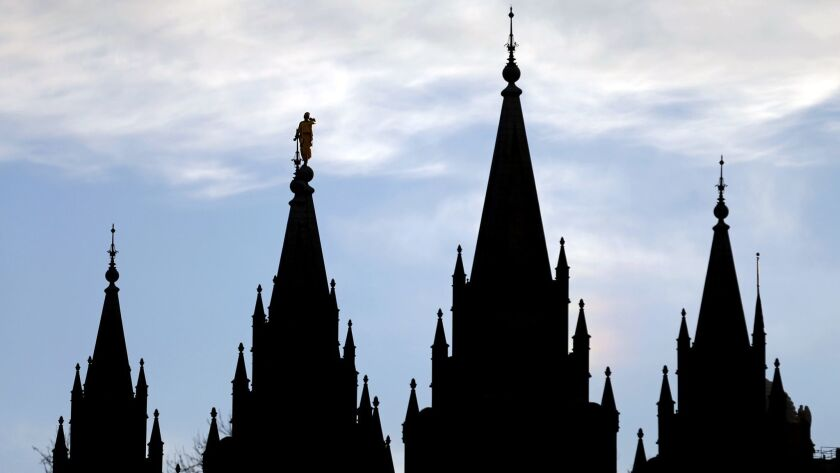 FILE- In this Jan. 3, 2018, file photo, the angel Moroni statue, silhouetted against the sky, sits a