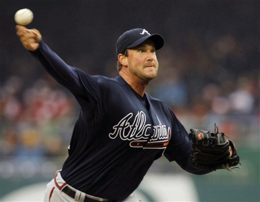 Atlanta Braves pitcher Derek Lowe throws the ball in the second inning of their opening day baseball game with the Washington Nationals on Thursday, March 31, 2011 in Washington.(AP Photo/Alex Brandon)