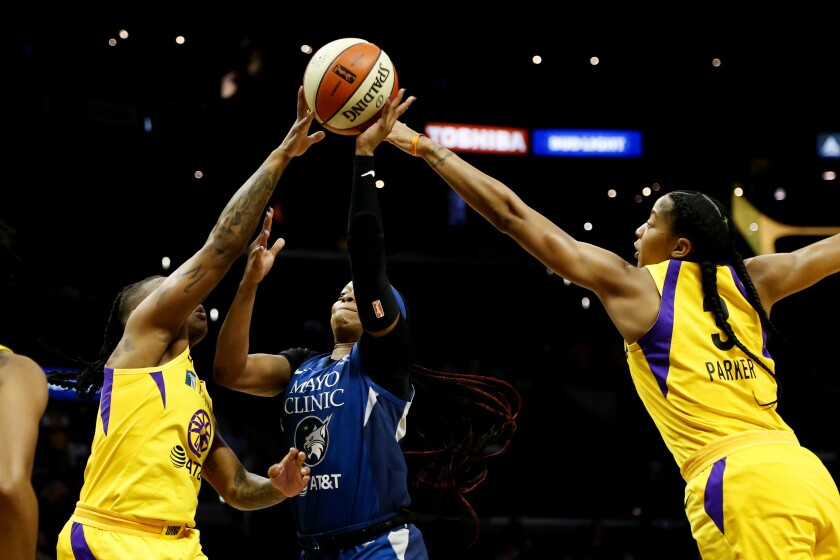 Sparks guard Riquna Williams and forward Candace Parker block a shot by Lynx guard Odyssey Sims during the first half Sunday.