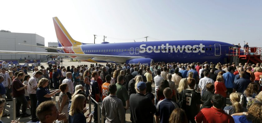 Southwest Airlines employees crowd around a newly unveiled plane paint color scheme during an event at Love Field Monday, Sept. 8, 2014, in Dallas. The change comes in a year during which 43-year-old Southwest has begun international flights, expanded in New York and Washington, and is freed from longtime government limits on its Dallas schedule. (AP Photo/LM Otero)