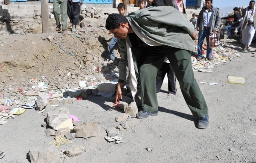 A Yemeni soldier inspects the site of the killing of Qassem Aqlan, a security investigator for the U.S. Embassy in Sana, Yemen.