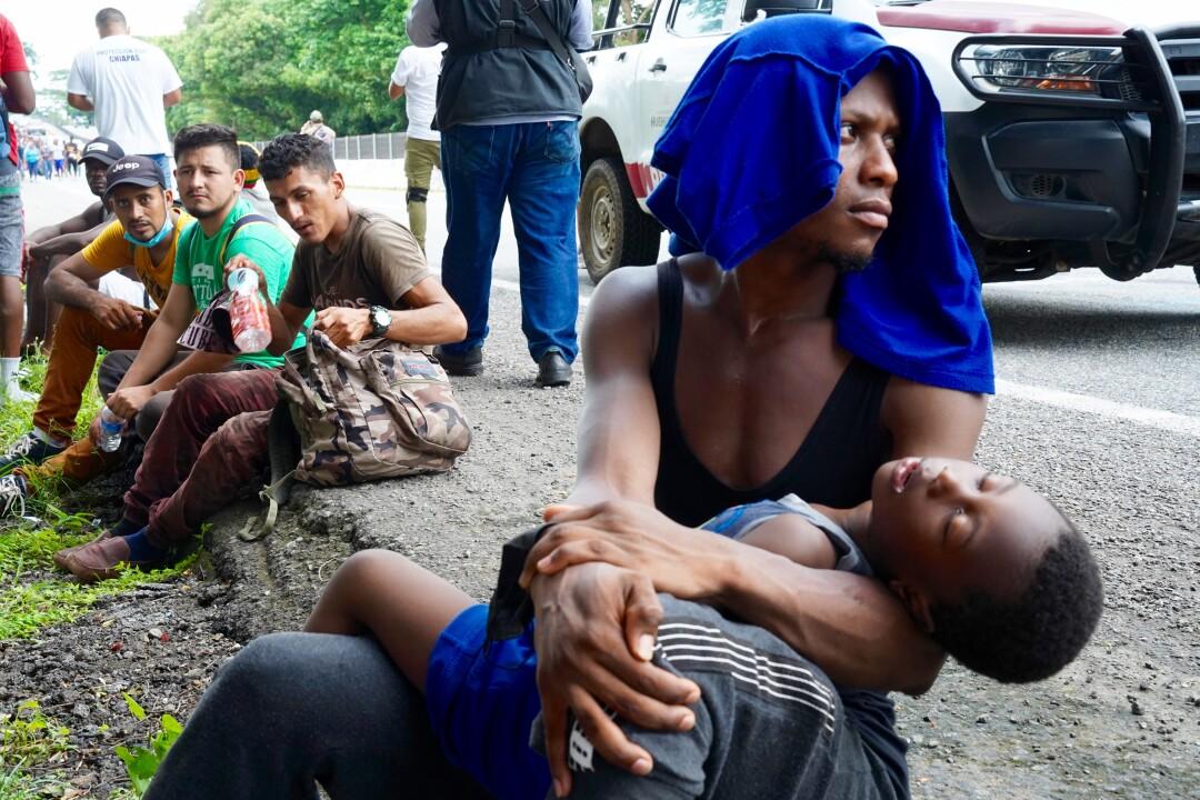 یک مهاجر یک کودک خسته را تاب می دهد