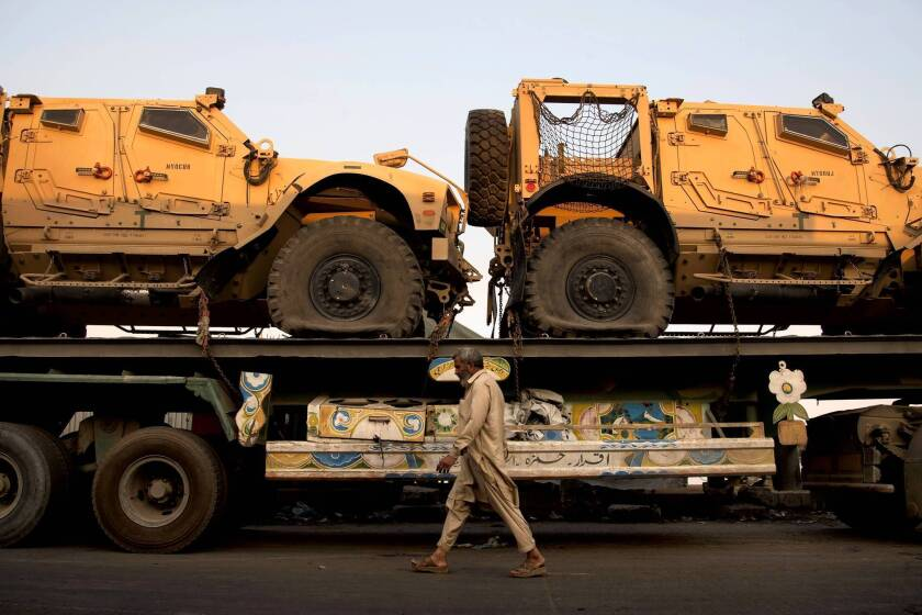 A truck carrying NATO military vehicles sits at a terminal in Karachi, Pakistan. Protesters have set up a blockade on a major highway into Afghanistan in hopes of ending the U.S. drone campaign in Pakistan.