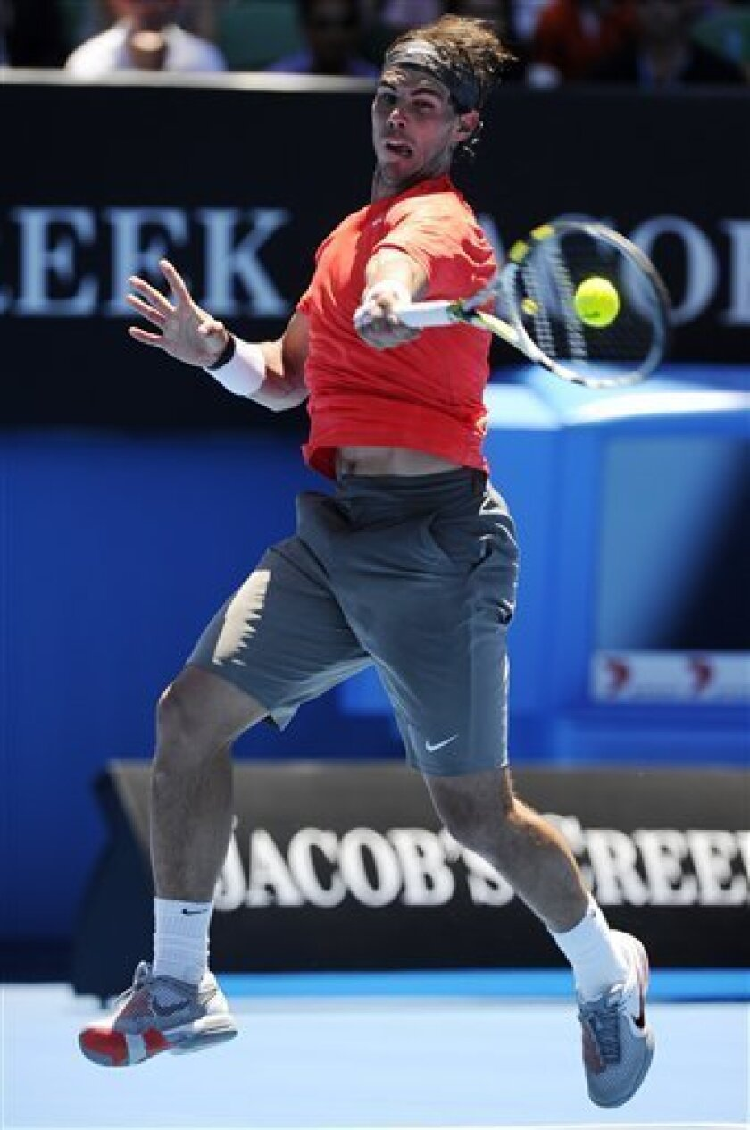 Spain's Rafael Nadal makes a forehand return to Ryan Sweeting of the U.S. during their second round match at the Australian Open tennis championships in Melbourne, Australia, Thursday, Jan. 20, 2011.   (AP Photo/Andrew Brownbill)