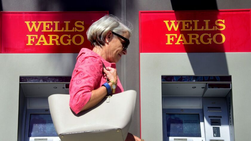 A woman walks past a Wells Fargo ATM in Pasadena last year.