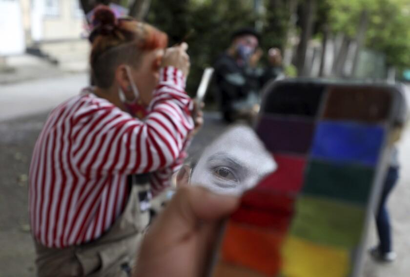 """Integrante de la compañía de circo se refleja en un pedazo de espejo mientras se prepara para una presentación en la calle en la que su grupo conocido como """"Circo Encuentro"""" actúa a cambio de donaciones de alimentos para ayudar a personas de bajo recursos en Bogotá, Colombia, el sábado 4 de julio de 2020. (Foto AP/Fernando Vergara)"""