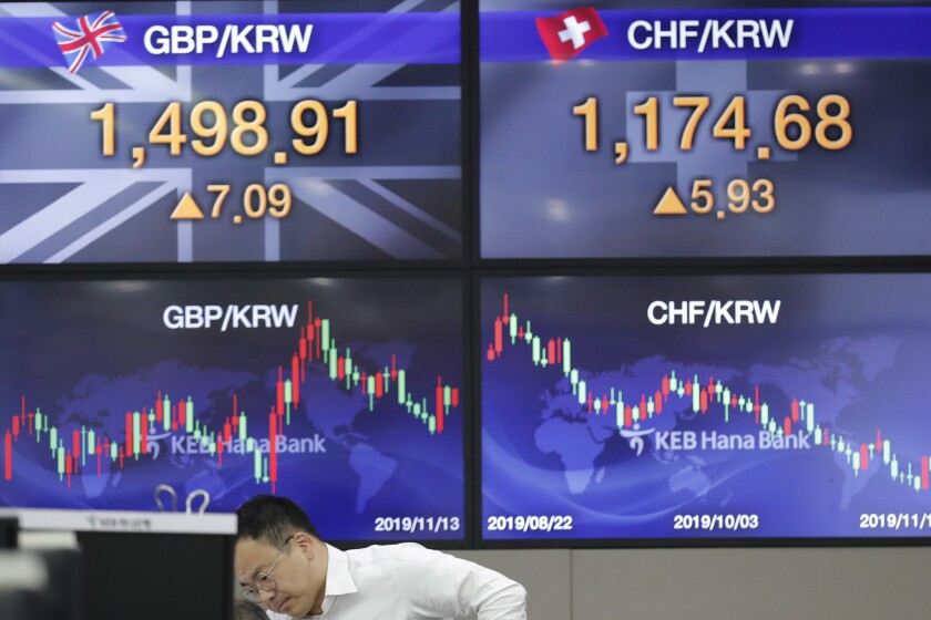 A currency trader works near the screens showing the foreign exchange rates at the foreign exchange dealing room in Seoul, South Korea, Wednesday, Nov. 13, 2019. Asian stocks sank Wednesday after U.S. President Donald Trump threatened more tariff hikes on Chinese imports if talks aimed at ending a trade war fail to produce an interim agreement. (AP Photo/Lee Jin-man)