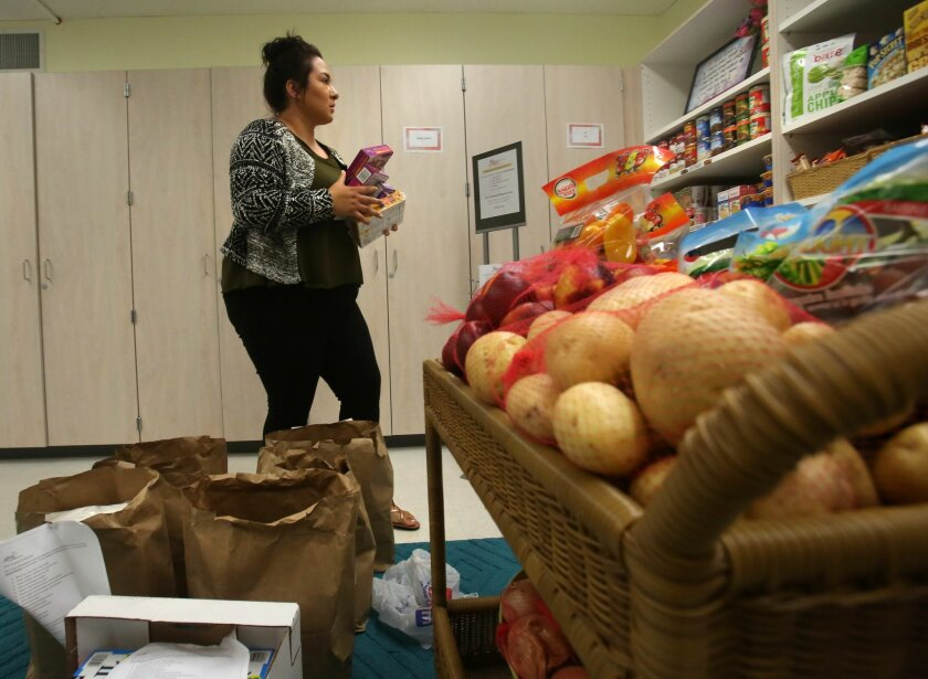 Naomi Oakes, a student at Southwestern Community College in Chula Vista, stocks the shelves at the school's JAG Kitchen Food Pantry in 2016.
