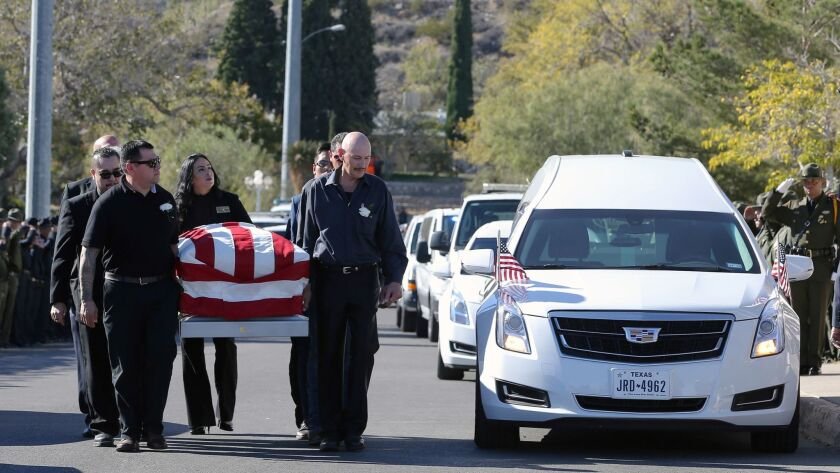 "Pallbearers carry Border Patrol Agent Rogelio ""Roger"" Martinez into Our Lady of Guadalupe Church in El Paso, Texas, for a funeral Mass on Nov. 25."